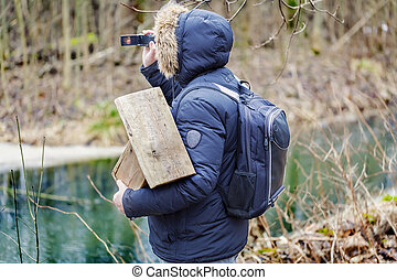 Ornithologist with camcorder and bird cage in the park near...