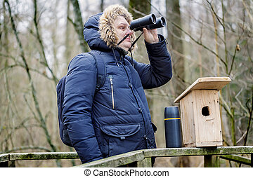 Ornithologist with binoculars and bird cage in the park on...