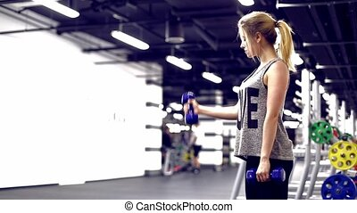 GYM Blonde girl pumps biceps - Blonde girl pumps biceps...