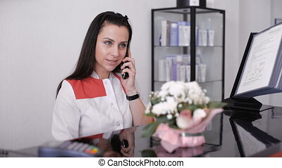 Portrait of a beautiful smiling nurse at desk station while talking on the phone.
