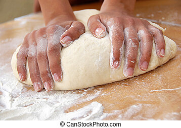 Hands on rolling pin over dough - woman hands rolling out...