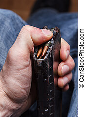Loading 5.56 ammo magazine for machine guns in hand