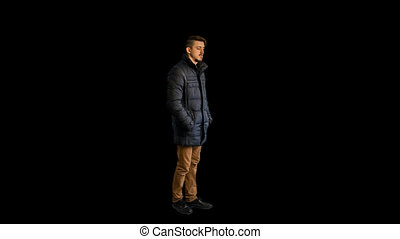 Man standing in a jacket, talking on the phone