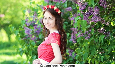 beautiful woman near lilac tree in spring park