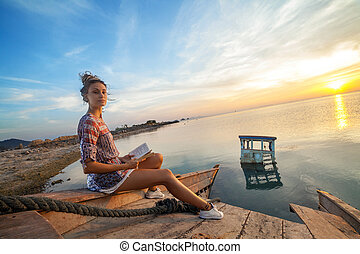 Young woman is sitting on the shipwreck and reading a book.