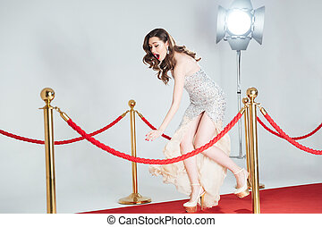 Woman falling on red carpet - Charming woman falling on red...