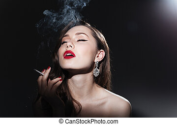 Beautiful woman smoking cigarette on black background