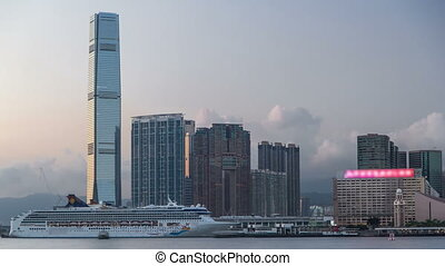 Hong Kong, China skyline panorama with skyscrapers from across Victoria Harbor evening timelapse.