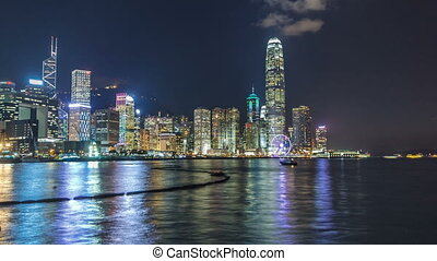 Hong Kong, China skyline panorama with skyscrapers at night from across Victoria Harbor timelapse.