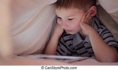 Boy lying under blanket and watching cartoon on touch pad -...