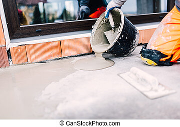 industrial worker on construction site pouring sealant from...
