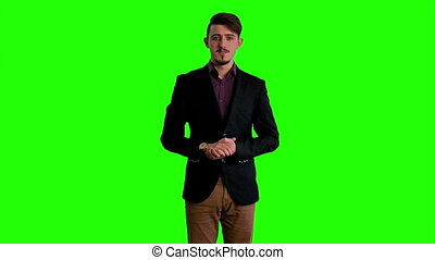 A man in a jacket standing at background of a green screen...