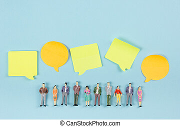 Real Estate concept. Blank speech bubbles and people toy figures Construction, building. Paper model house with key on blue background. Top view. Copy space for text.