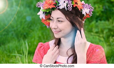 beautiful woman with a wreath on a green meadow