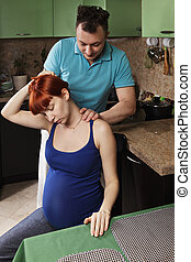 Guy making massage to pregnant woman at the kitchen