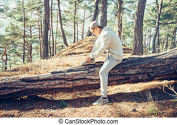 Man tying shoelaces in the forest - Sporty young man sitting...