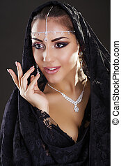 Portrait of a beautiful woman with arabian makeup in black...
