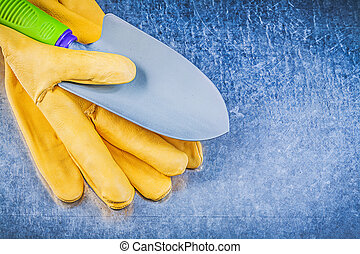 Yellow safety gloves metal hand spade on metallic background...