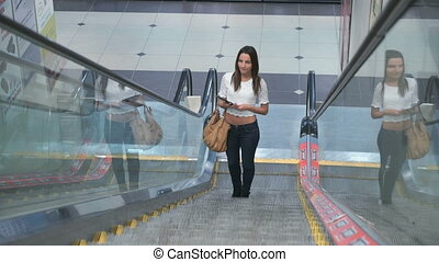 Stylish fashionable girl rides on an escalator - Stylish...