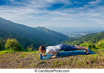 Woman practices yoga asana Chaturanga Dandasana - Beautiful...