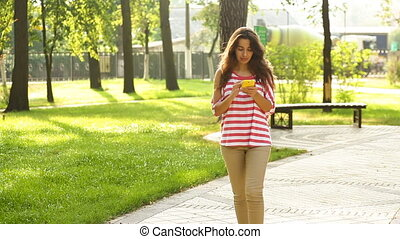 beautiful woman with a phone goes on summer park
