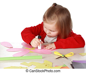 girl playing with paper and glue - Cute little girl making a...