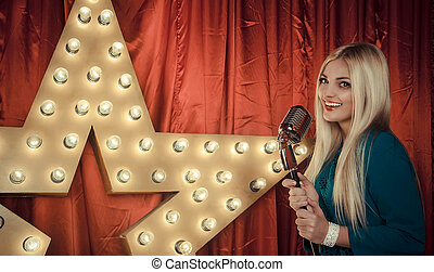 Beautiful woman singing on stage with microphone