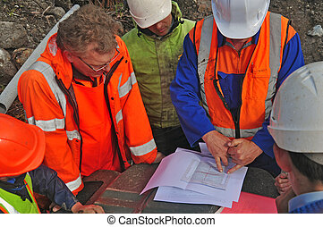 discussing the survey - Geologists in the field discuss the...