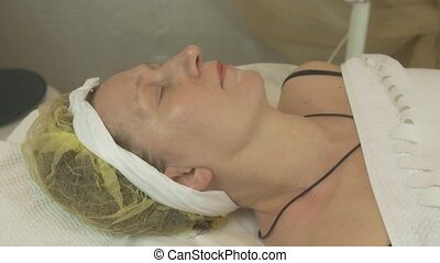 Adult woman lie in beauty saloon under white blanket. Anti...