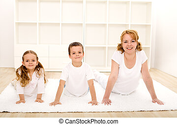 Happy healthy kids and woman doing gym exercises