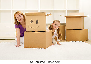 Happy woman and little girl unpacking and having fun in a...