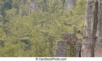 Climber Girl Down From The Cliff on a Rope