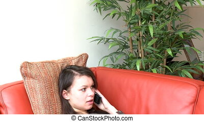 Pensive woman talking on phone sitting on sofa at home