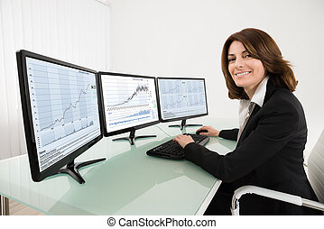 Female Stock Market Broker Working On Multiple Computers