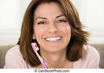 Young Woman Brushing Her Teeth With Toothbrush At Home