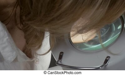 Cosmetologist look in magnifier Process of dyeing eyelashes...