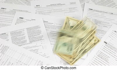 Dollars and Coins on Tax Forms - Dollars and coins thrown on...