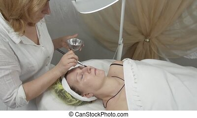 Cosmetologist put water on adult woman face by brush in...