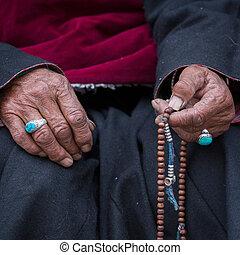 Old Tibetan woman holding buddhist rosary, Ladakh, India...