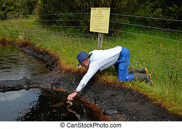 oil seep - An oil prospector samples crude oil from a...