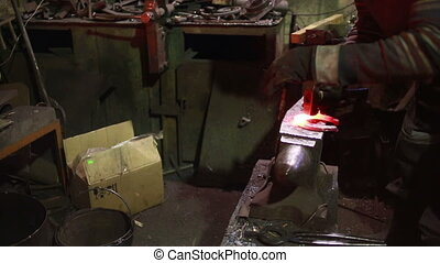 The smith in a smithy forges a horseshoe hot iron