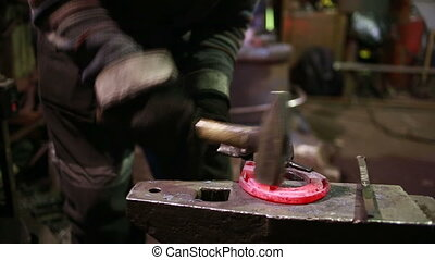 The smith in a smithy forges a horseshoe. hot iron