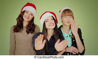 Group of girls in Christmas hats posing and send greetings -...