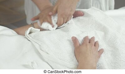 Cosmetologist clear left hand of adult woman by wet napkin...