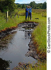 oil seep - A couple of oil prospectors take GPS readings at...