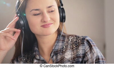 Young beautiful woman lying on the sofa and listening music in her headphones on the living room.