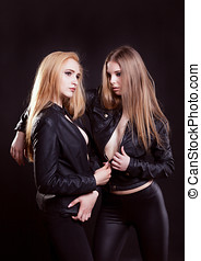 Two sexy women in leather jacket and no bra on black...