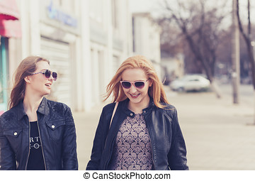 Two female friends enjoying a walk in sunny wheather outside...