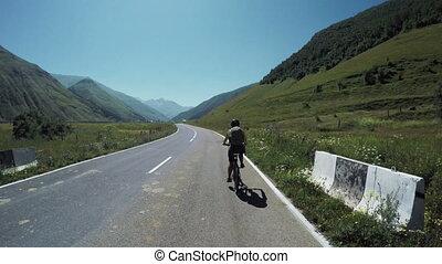 Girl on bike in mountains - On mountain road in Georgia girl...