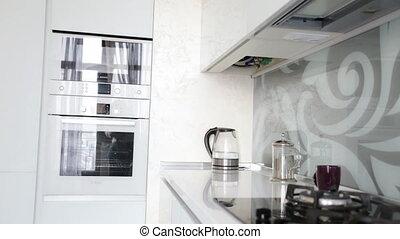 Beautiful woman turning on modern glass electric kettle on...